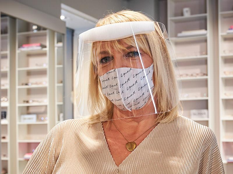 Optiker i visir och munskydd